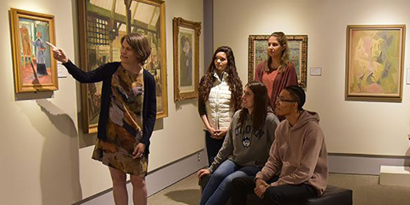 Assistant Curator/Academic Liaison, Amanda Douberley points and describes a painting to four undergraduate students in the Gilman Gallery at The Benton Museum of Art, UConn