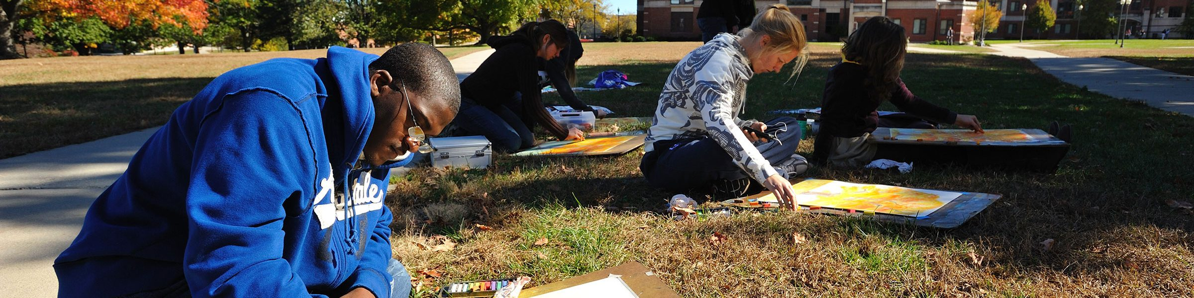 Four UConn Art & Art History students sitting and working with pastels in the south quad lawn during the Fall
