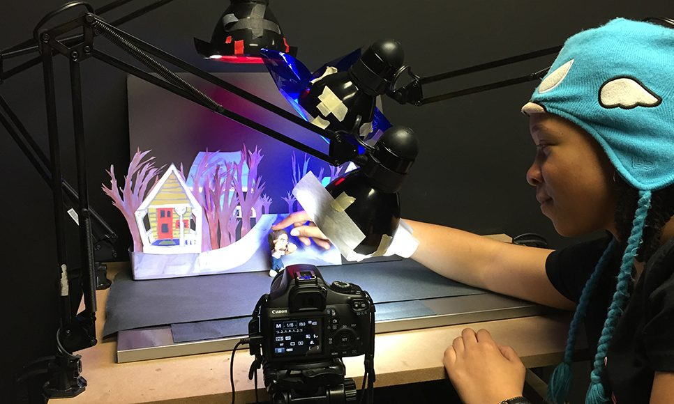 Behind a camera and lamp, a student adjusts subject in winter claymation scene, UConn Art and Art History