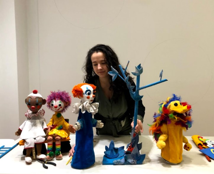 puppet artist behind a table of puppets